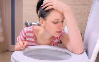 Schwangerschaft Symptome Frau mit Übelkeit und positivem Schwangerschaftstest